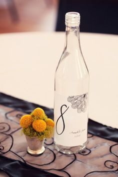 Couples are always looking for cool and unusual ways to name/mark their guest tables.  I like this idea of using a bottle of water with a custom label.