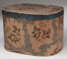 "MARYLAND FAMILY BONNET AND HAT BOX, the woven straw bonnet with net lining, fitted in a block-printed wallpaper covered pasteboard oval box, both with accession-type number. Circa 1832. Box 11 1/4"" H, 12 1/4"" x 17""."