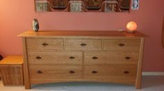 A laid back bedroom with a beautiful handcrafted wood dresser from Vermont Woods Studios.