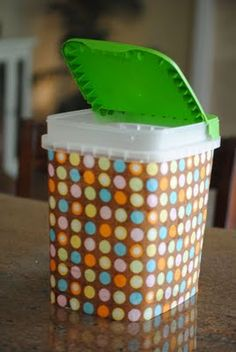 Repurpose an empty dishwasher tablet container in to a trash bucket for tables with a little fabric and mod podge.
