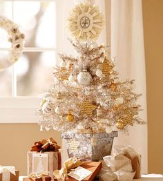 Deck your holiday table in silver and gold with this timeless tabletop Christmas tree. A pint-size silver faux tree adorned with handmade ornaments created from cast-off materials stands in a small galvanized pot.