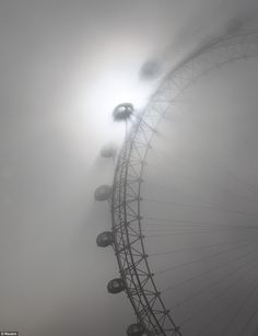 The pods on the London Eye tourist attraction cast shadows against a thick morning fog