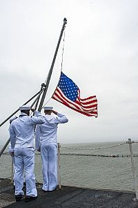 #USNavy Sailors raise the national ensign on the flight deck of the aircraft carrier USS Harry S. Truman.