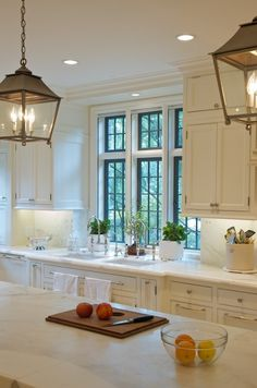 White kitchen,  lanterns, & dark windows.