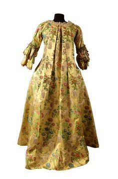 Robe à la française (back), 1740, France, Yellow satin, brocaded silk with naturalistic background polychrome decorated with shrubs and flower bouquets.  Pagoda sleeved bodice with 2 pleated ruffles. (c) Photo Coutau-Begarie