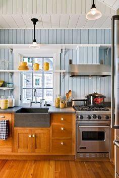 Love almost everything about this: open shelving, modern farmhouse sink, warm wood, pop of color with the dishes, white trim and wainscot. The stove is a bit small, and shoved to a corner though
