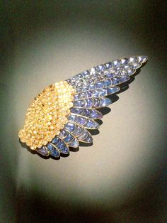 A Spectacular Sapphire and Diamond Brooch, by Rene Boivin, circa 1936, designed as a pigeon's wing pave-set with circular and baguette-cut diamonds and calibre-cut sapphires, mounted in platinum, subsequently gilt.  Est $50,000 to $75,000