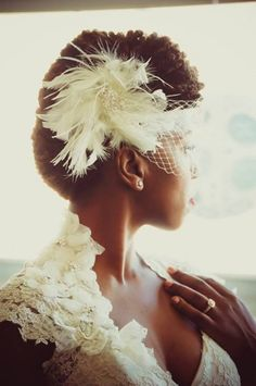 feathers, ribbon, crystal, etc. are great way to glam up your wedding day 'do! just check out this feathered birdcage veil on this bride's twist up-do; fabulous! #naturalbride #naturalstyle #weddingstyle #updo #natural
