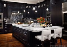 Dark kitchen with white carrara marble and white chairs.