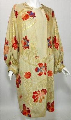 Orientalist style 1920s ivory silk   opera coat shot with metallic gold   fauna design setting of velvet pile   nouveau florals in rich flame and   purple hues. Lame' gold cuffs   ruched below full sleeves. Padded   inside for structure, lined in ivory   silk velvet. Hook an   eye closure at neck (may have had   a fur collar at some point). Exterior   of coat in flawless condition. Source: Dorotheas Closet Vintage