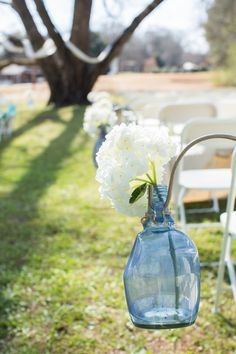 Hydrangeas in blue glass jugs served as aisle markers. // Photo by Erin Lindsey Images Flowers from Wholesale Florist of Huntsville