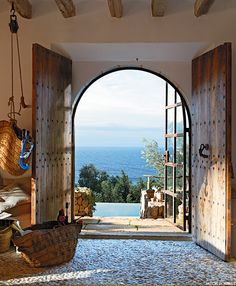 Rustic double entry doors, arched doorway, exposed beam ceiling with an ocean view. Gorgeous!
