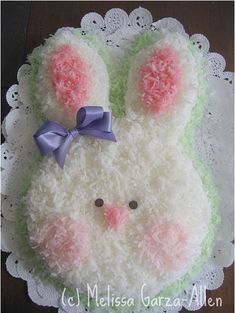 . Soooo  Cute !  Have made this with two round cake layers.  One whole layer for face.  Cut to ears (one crescent off each side of other layer) and that leaves a bow shaped piece to put under the face as a bow tie.  Ice and add coconut!