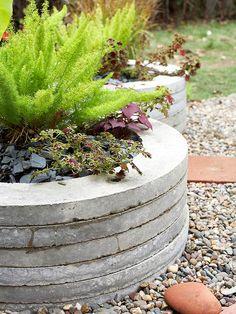 stacks of precast concrete manholes.  unique planters