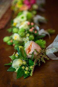 Bountiful boutonnieres with pops of peach.