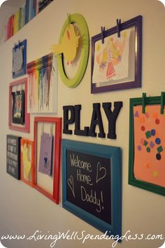 Playroom gallery wall & kids artwork display.  Post includes instructions for making clothespin frames, chalkboard, & crayon art, plus tips on how to hang it all perfectly!