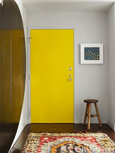 The front door in a Chicago apartment designed by Richard Bories and James Shearron, is highlighted with Benjamin Moore's Bright Yellow on the back.