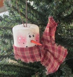 Ornament is made out of a marshmallow. He has a toothpick for this nose and a piece of fabric has been wrapped around the bottom for this scarf. The hanger is a rusted wire.