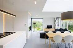 Open witte leefruimte met keuken en zithoek op grijze epoxy vloer