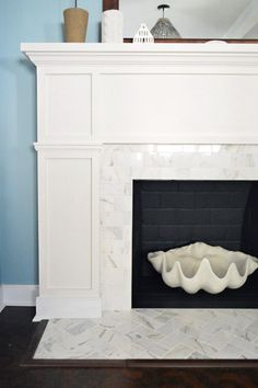 Fireplace makeover with white marble subway tile from Home Depot. Love the herringbone pattern on the hearth.
