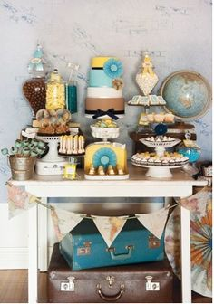 Travel themed dessert table. This will be in the room. Mixture of vases, buckets, and small luggage cases.
