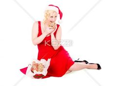 girl biting into a cookie - Girl in red holiday attire sitting on white biting into a gingerbread cookie. MUA and Model: Amanda Wynne