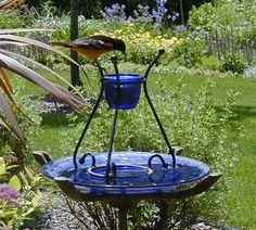 This homemade jelly feeder uses an old birdbath as the base, which serves as an ant guard too. via BirdsandBloomsBlo...