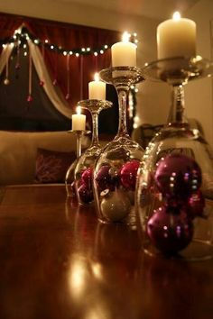 Upside down wine glasses with ornaments, topped with a candle. Great, simple centerpiece for Christmas dinner!