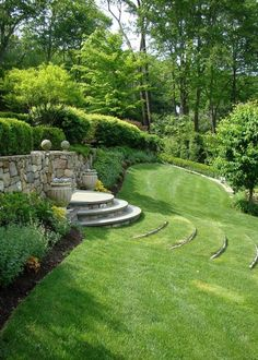 gradual, curved steps covered in grass in the garden, stone fence retaining wall