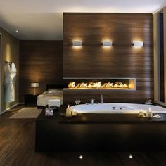 Inspiration from Bathrooms.com: Low lighting, wooden panelling in dark shades and a bath set into a generous surround all add up to a grown-up feel. #bath #bathroom #spa #wetroom