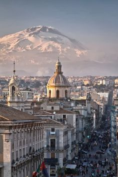 Catania, Sicily. and Mt. Etna volcano covered by snow in the background