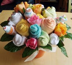 A bouquet made from onesies, baby socks, baby hats and washcloths. The next baby shower I get to go to ...