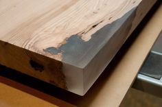 "Around the ""live edges"" of the slab, Stacklab had to apply an epoxy to square off the corners of the bar."