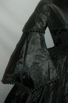 "Splendid 1860's Civil War Black Silk Mourning Dress  eBay- fiddybee; over sleeve & hem of sleeve trimmed with black silk & black chenille velvet balls, same with bodice front, piping at neck, armscyes & waist; bodice cotton lined with front hook & eye closure, skirt attached w/ cartridge pleating, unlined except band of cotton at hem; some underarm discoloration on lining; some small holes & splits; bust: 34""; waist: 26""; skirt length: 42""; width at hem: 144"""