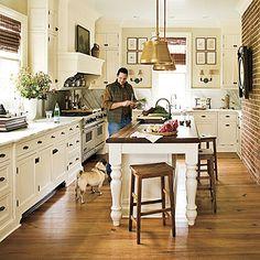 kitchen love - bras pendant lighting, butcher block island, marble counter top with extending marble back splash.