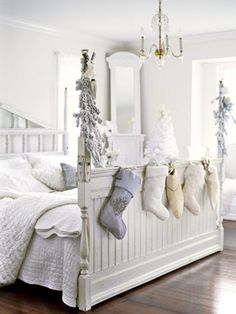 An array of cozy stockings in different colors and textures at the foot of this bed.