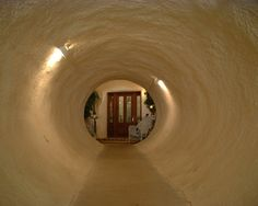 In something out of a james bond film intro, this entryway to an underground house features a concrete tunnel leading into a very conventional upscale entryway