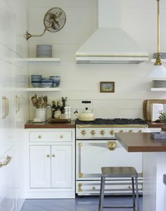 stove, ceiling fan in kitchen, brass, kitchen hoods, corner shelves, white gold, open kitchens, gold accents, white kitchens