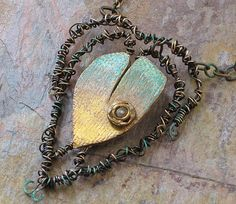 Entwined Heart - polymer and wire-- by Christine Damm   Polymer clay heart, bronze wire -- twisted and antiqued-- antique button. The clay was colored with guilders paste on textured ivory clay.