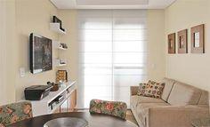 Manter a TV suspensa foi a solução para ganhar espaço no rack (2,25 x 0,40 x 0,60 m). Os mimos exibidos em nichos e prateleiras imprimem no visual a personalidade de Aline. O piso laminado de cor clara foi aplicado em todos os ambientes secos. À frente do sofá, o tapete de sisal aquece a área.Persiana: De taboa (1,60 x 2,20 m). Luri, R$ 1 350.Rack de MDF: Combina laminado branco e madeira.