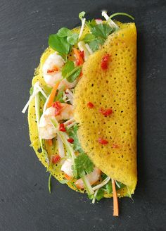 Bánh Xèo: Ingredients ― For the pancakes ~ rice flour; egg; salt; turmeric; coconut milk; oil. For sauce ~ lime juice; toasted sesame oil; brown sugar; soy sauce; ginger; red chile; garlic. For filling ~ carrot; daikon radish; onions; green chili; sugar snap peas; cilantro; basil; mint; mung bean sprouts; enoki mushrooms. Instructions ― Make pancake batter. Make the sauce. Make filling. Cook pancakes. Place pancakes on a plate; top with vegetables, drizzle with sauce, fold. Serve. #BanhXeo