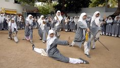 """Muslim schoolgirls from St. Maaz high school practise Chinese wushu martial arts inside the school compound in the southern Indian city of Hyderabad July 8, 2008. Girls from ages 10 to 16 participate in weekly sessions during school term."""