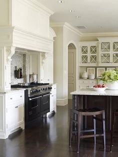 white kitchen cabinet legs espresso island criss-cross paned cabinets Pottery Barn barstools dark wood floors
