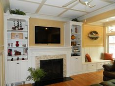 Custom-designed painted and glazed cabinetry surrounds fireplace, and a generous space is set for a built-in home entertainment system and bench in this traditional den. Golden paint and floors create contrast.
