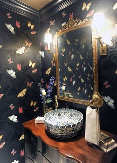 Ornate vanity and butterfly wallpaper in a powder room.