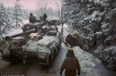 An American Sherman M4 tank moves past another gun carriage that slid off icy road in the Ardennes Forest during the push to halt advancing German troops, c. 1944-1945.