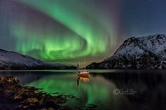 A fishing boat sits in a fjord in Norway surrounded by auroras. Credit and copyright: Frank Olsen.