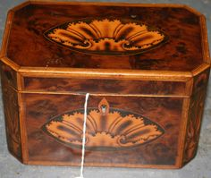 A George III yew tea caddy, the hinged lid and front inlaid with shell paterae within crossbanded borders, the canted corners and sides inlaid with urns and flowers, width approx 19cm. from Tooveys