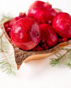 Fill wood bowls with beautiful fruit, such as rich, red pomegranates and cranberries.