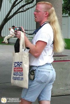 Blonde mega mullet.  Acid washed jean shorts. Cell phone clipped to jean shorts. Camera strap securely fastened around neck. How is he not mine?